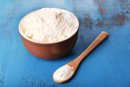 butterfat: Fresh homemade butter in bowl, on color wooden background