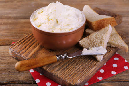 butterfat: Fresh homemade butter in bowl and sliced bread, on wooden background