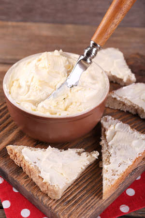Fresh homemade butter in bowl and sliced bread, on wooden background photo