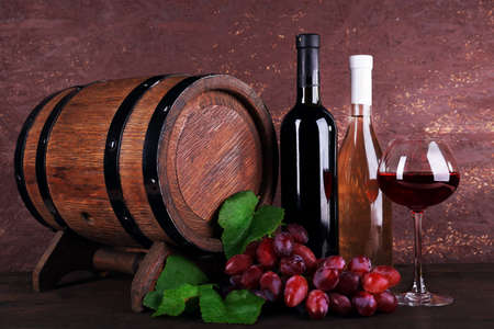 Wine in bottles and in goblet, grapes and wooden barrel on wooden table on wooden background photo