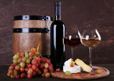 Supper consisting of Camembert cheese, wine and grapes on cutting board and wine barrel on wooden table on brown background photo