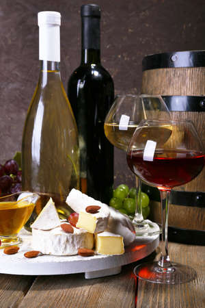 Supper consisting of Camembert cheese, honey, wine and grapes on stand and wine barrel on wooden table on brown background