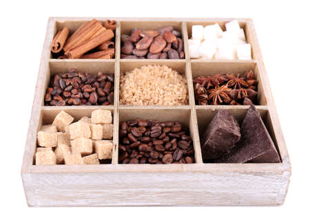 Wooden box with set of coffee and cocoa beans, sugar cubes, dark chocolate, cinnamon and anise, isolated on white photo