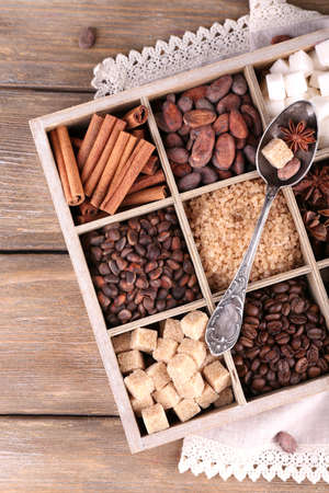 Wooden box with set of coffee and cocoa beans, sugar cubes, dark chocolate, cinnamon and anise, close-up, on wooden background photo