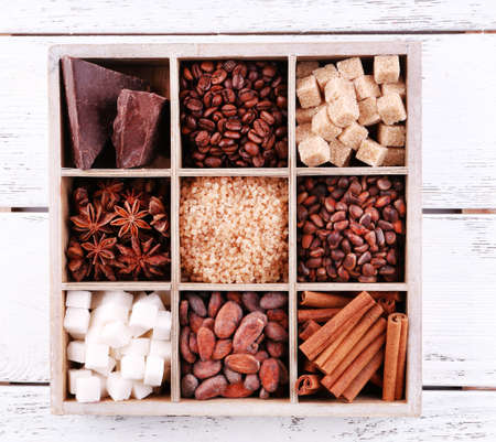 Wooden box with set of coffee and cocoa beans, sugar cubes, dark chocolate, cinnamon and anise over wooden background photo