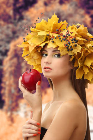 Beautiful young woman with yellow autumn wreath and apple outdoors photo