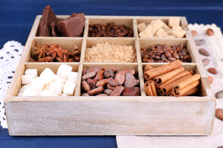 Wooden box with set of coffee and cocoa beans, sugar cubes, dark chocolate, cinnamon and anise on wooden background photo