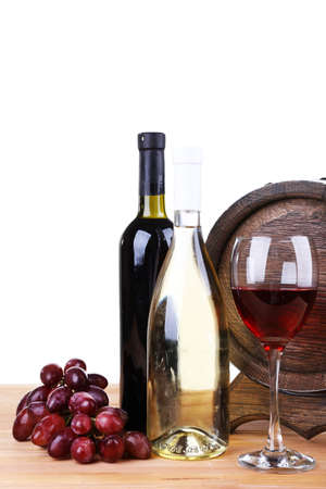 Wine in goblet and in bottles, grapes and barrel on wooden table on white background photo