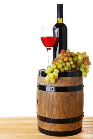 Wine in goblet and in bottle and grapes on barrel on wooden table on white background photo