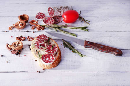 Sandwich with salami, rosemary and walnuts on wooden background photo