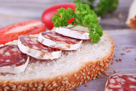 French salami with tomatoes, parsley and bread on cutting board on wooden background photo