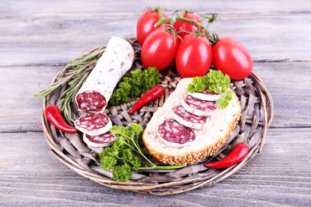 French salami with tomatoes, bread and parsley on wicker mat on wooden background photo