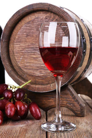 Red wine in goblet, grapes and barrel on wooden table on white background photo