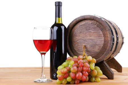 Wine in goblet and in bottle, grapes and barrel on wooden table on white background photo
