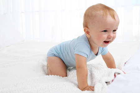 Cute baby boy on bed in room Stock Photo