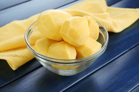 Raw peeled potatoes in glass bowl  on color wooden background photo