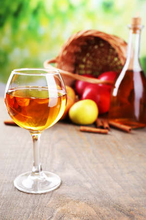 Apple cider in wine glass and bottle, with cinnamon sticks and fresh apples on wooden table, on bright background photo