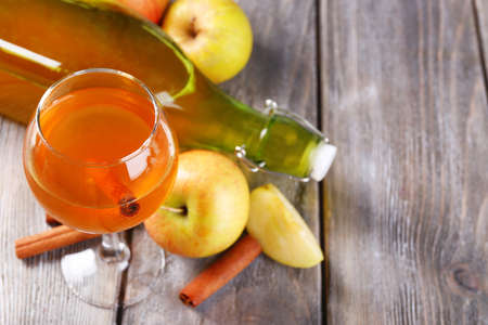 Apple cider in wine glass and bottle, with cinnamon sticks and fresh apples on wooden background Stock Photo
