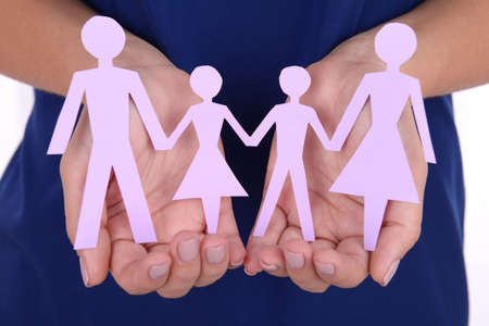 Woman hands holding paper family close up photo