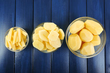 Raw peeled and sliced potatoes in glass bowls  on color wooden background photo