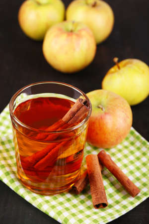 Apple cider with cinnamon sticks and fresh apples on wooden background photo