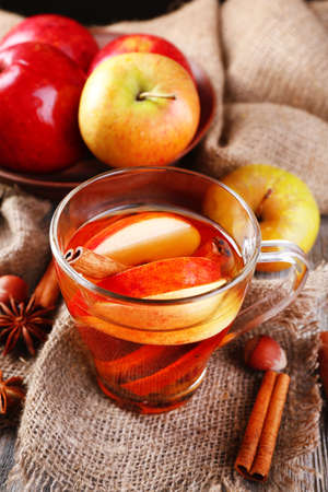 Apple cider with cinnamon sticks, spices and fresh apples on wooden background photo