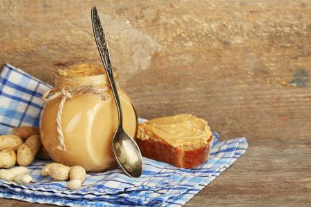 Fresh peanut butter in jar on wooden background photo