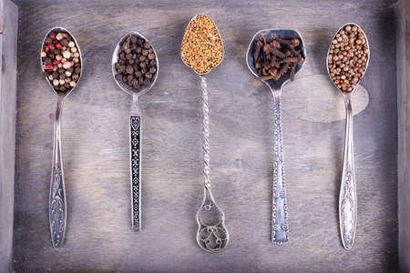 seasonings: Seasonings in metal spoons on wooden background