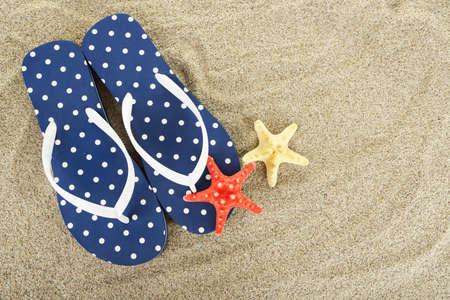 Flip flops on sea sand background photo