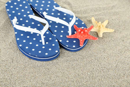 Flip flops on sea sand background photo