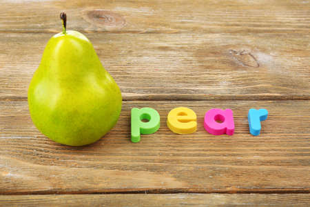 Pear word formed with colorful letters on wooden background photo