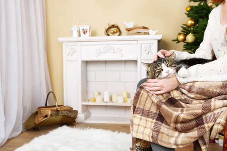 Woman and cute cat sitting on rocking chair in the front of the fireplace photo