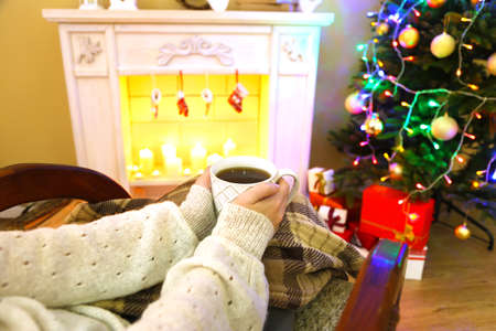 Woman holding cup of hot drink in front of fireplace photo