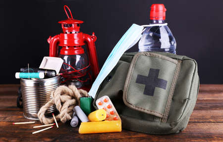 food supply: Emergency preparation equipment on wooden table, on dark background