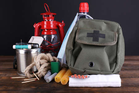 disaster: Emergency preparation equipment on wooden table, on dark background