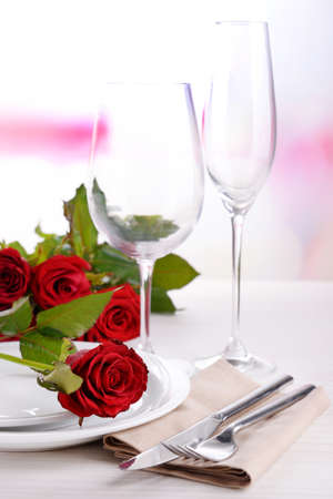 Table setting with red rose on plate photo