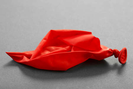 popped: Popped red balloon on paper background Stock Photo
