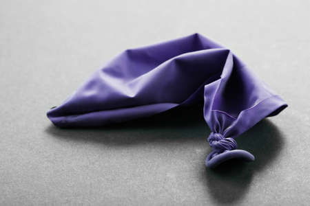 popped: Popped violet balloon on paper background