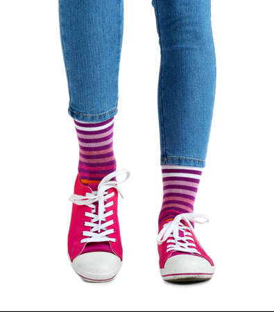 Female legs in colorful socks and sneakers isolated on white photo