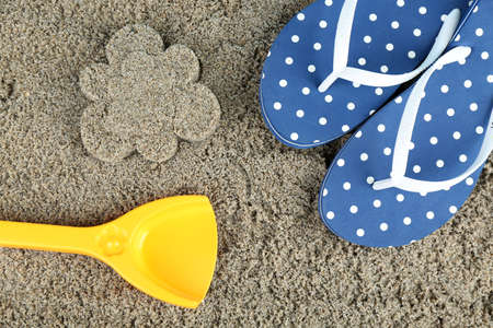 Flower-shaped wet sand and flip flops, close-up photo
