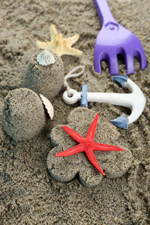 sand mold: Flower-shaped  and castle-shaped sand, starfish and children toys close-up Stock Photo