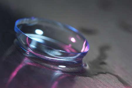 lentes de contacto: Lente de contacto con gotas de agua en el fondo brillante
