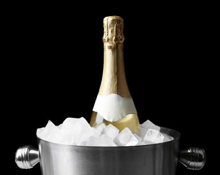 Bottle of champagne in bucket with ice, on black background photo