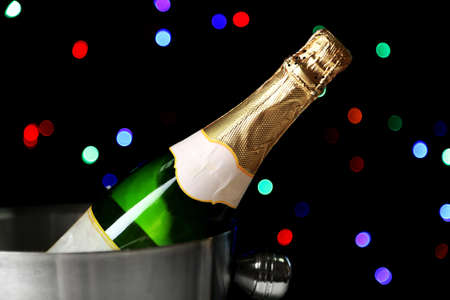 Bottle of champagne in bucket, on black background with color lights