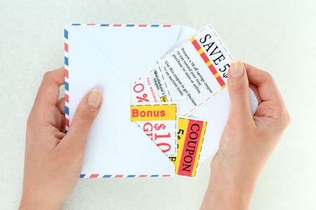 Set of cut coupons in hand with envelope