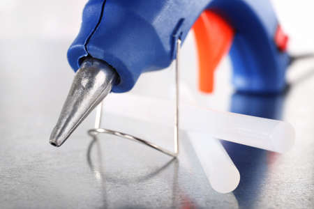 silicone: Dark blue glue gun and silicone stick on light background Stock Photo