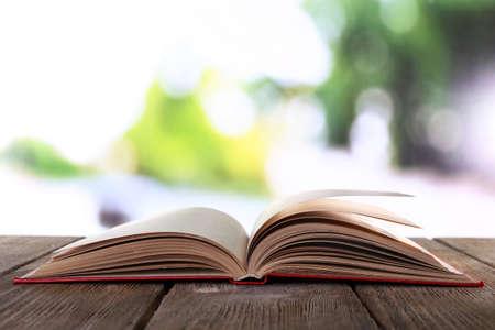 jeden: Otevřená kniha na dřevěném stole na přírodním pozadí