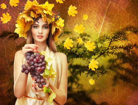 Beautiful young woman with grapes and yellow autumn wreath outdoors photo