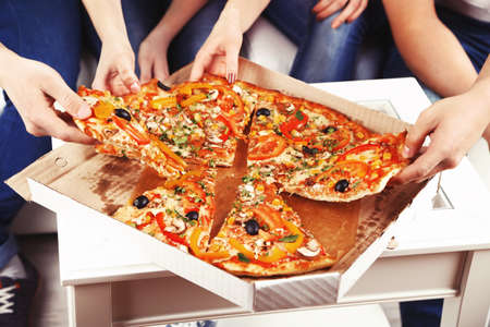 cool colors: Group of young friends eating pizza in living-room on sofa Stock Photo