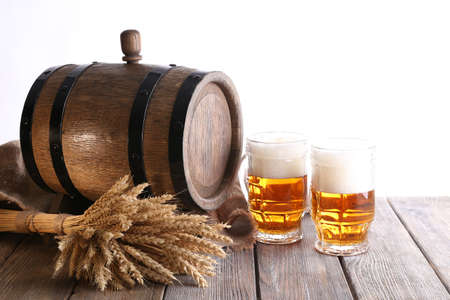 Beer barrel with beer glasses on table on white background photo
